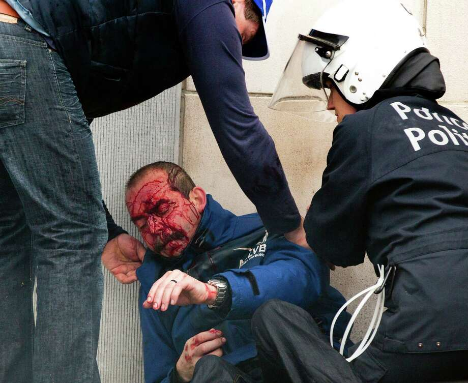 Police help an injured colleague during a trade union demonstration in the European Quarter of Brussels on Friday, April 4, 2014. A demonstration by labor unions demanding a better deal for Europe's working men and women led to street clashes in Brussels Friday, with some protesters showering police with oranges and cobblestones and police responding with water cannon. Photo: Virginia Mayo, AP  / AP