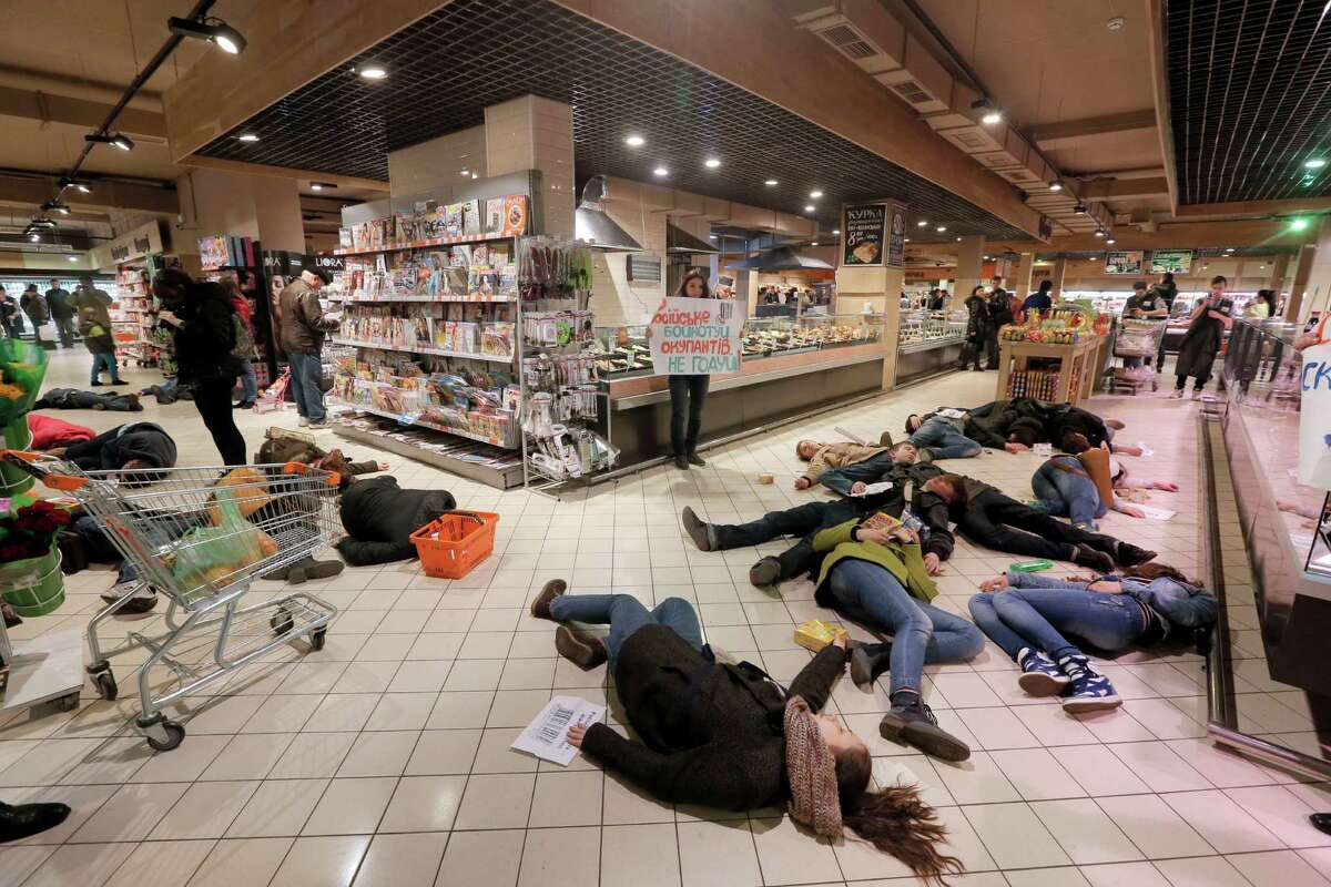 Ukrainians lay on a store's floor, acting as dead bodies in a flash mob action protesting against buying of the Russian goods in Kiev, Ukraine, Saturday, April 5, 2014. Writing on posters reads