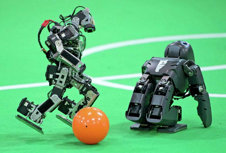 A robot of a German team, left, plays the ball besides a British team robot in the Kids League at the RoboCup German Open 2014 in Magdeburg, Germany, Thursday, April 3, 2014. 44 international RoboCup Major League teams from 12 countries demonstrate the state-of-the-art competitions in soccer, rescue and service robots. The RoboCup German Open takes place from April 3 to April 5, 2014. Photo: Jens Meyer, AP  / THE ASSOCIATED PRESS2014