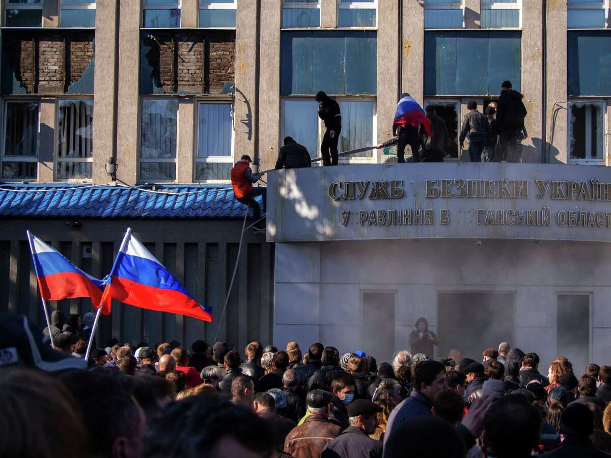 Pro-Russian activists with Russian national flags storm the Ukrainian regional office of the Security Service in Luhansk, Ukraine, Sunday, April 6, 2014. In Luhansk, 30 kilometers (20 miles) west of the Russian border, hundreds of people surrounded the local headquarters of the security service and later scaled the facade to plant a Russian flag on the roof.