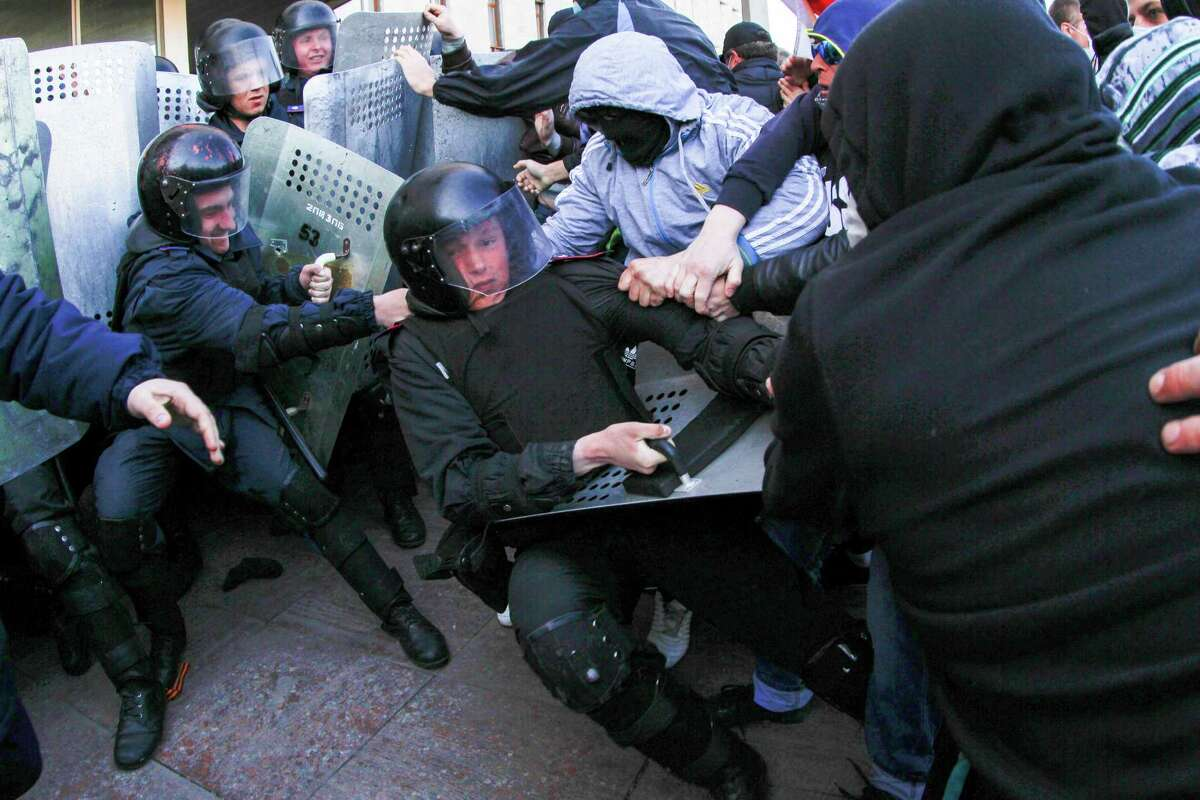 Pro-Russian activists clash with police at the regional administration building in Donetsk, Ukraine, Sunday, April 6, 2014. In Donetsk a large group of people surged into the provincial government building and smashed windows. A gathering of several hundred, many of them waving Russian flags, then listened to speeches delivered from a balcony emblazoned with a banner reading