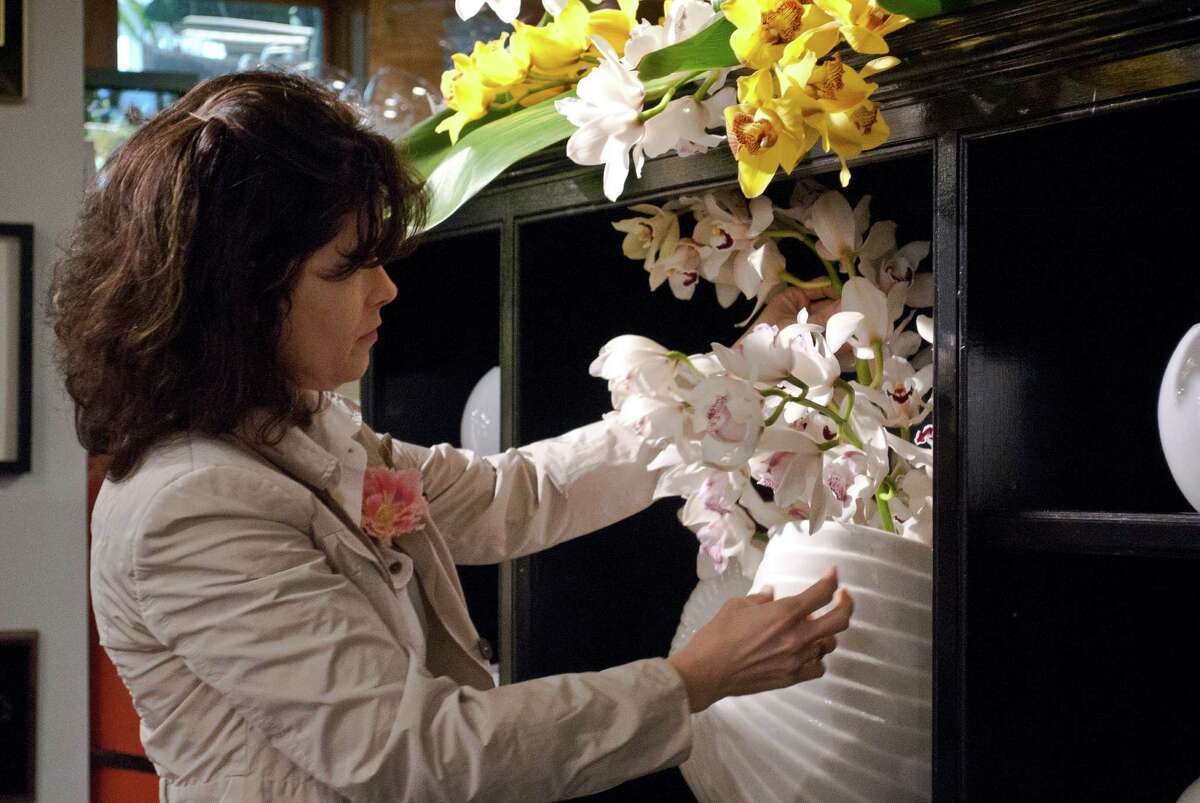 Nielsen's Florist and Garden Shop in Darien held a flower show to celebrate their 70 year anniversary of being in business from April 4-6. Dana Burwell, from New Canaan, adjusts one of the displays.