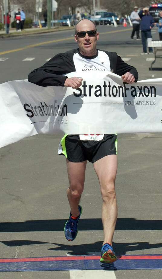 Mark Hixson crosses the finish line to win the Stratton Faxon Greater Danbury Half Marathon, in Rogers Park, Danbury, Conn, on Sunday, April 6, 2014.. Photo: H John Voorhees III / The News-Times Freelance
