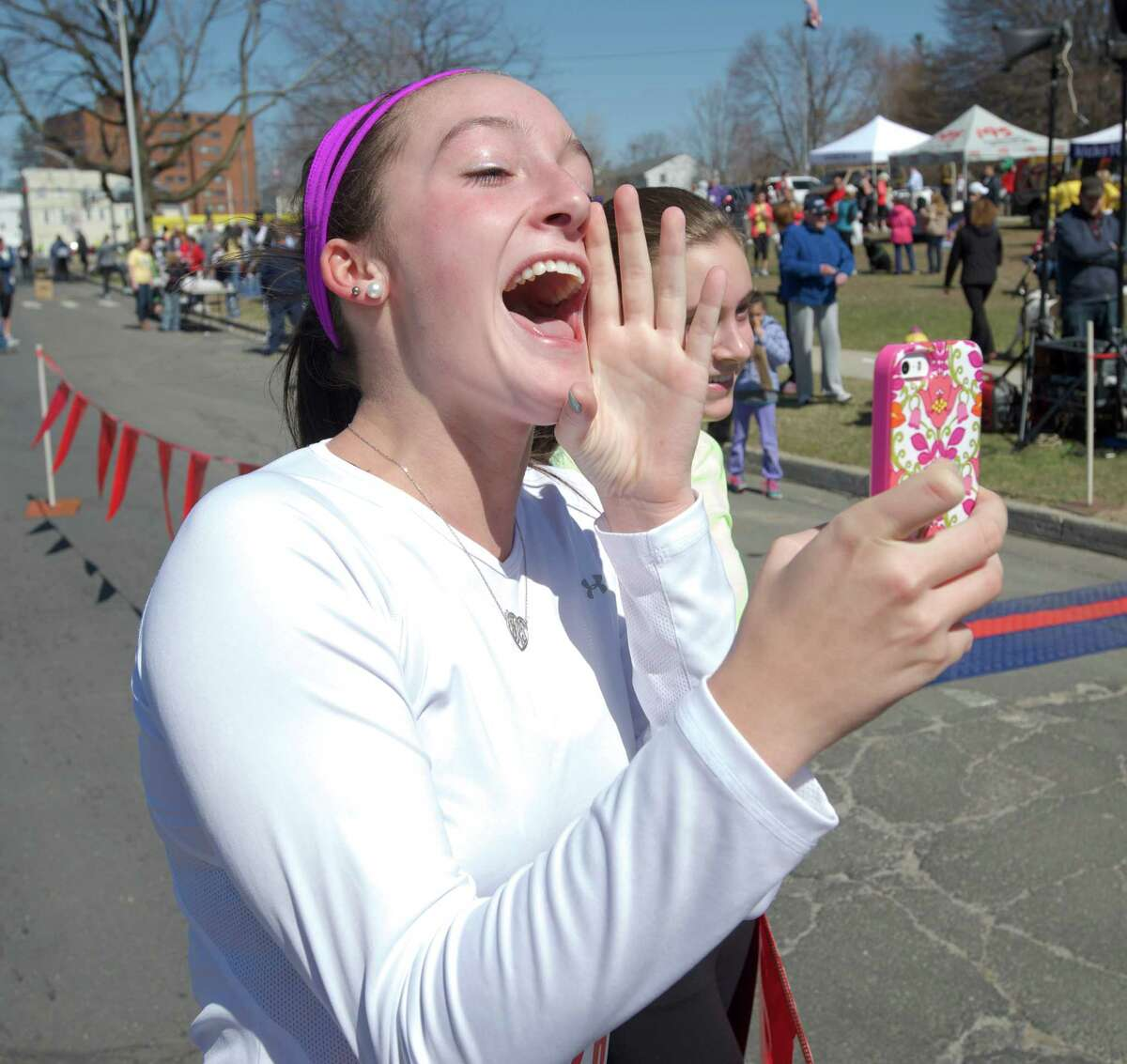 Jessica Roth, age 18, of Danbury, waits at the finish line with her sister Jordan Roth, age 15, for their parents Jennifer and Jeffery Roth to finish the Stratton Faxon Greater Danbury 5K, all four ran in the race, in Danbury Conn, on Sunday, April 6, 2014.