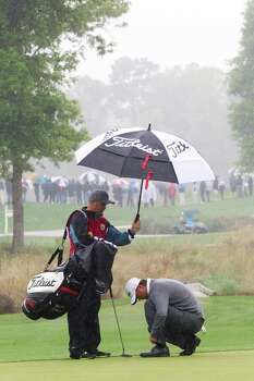 Matt Jones fixes his shoe laces under the rain as he approaches the ninth hole green during the championship round of the Shell Houston Open at the Golf Club of Houston, Sunday, April 6, 2014, in Humble. Photo: Marie D. De Jesus, Houston Chronicle / © 2014 Houston Chronicle