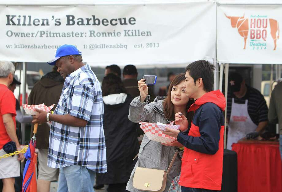 Maeka Inoue and Junya Ionue take a selfie during The 2nd Annual BBQ Cook Off on April 6,  2014, in Houston, Tx. The Houston Barbecue Festival is to celebrate and recognize owners and pit masters that make Houston barbecue unique. Photo: Mayra Beltran, Houston Chronicle / © 2014 Houston Chronicle