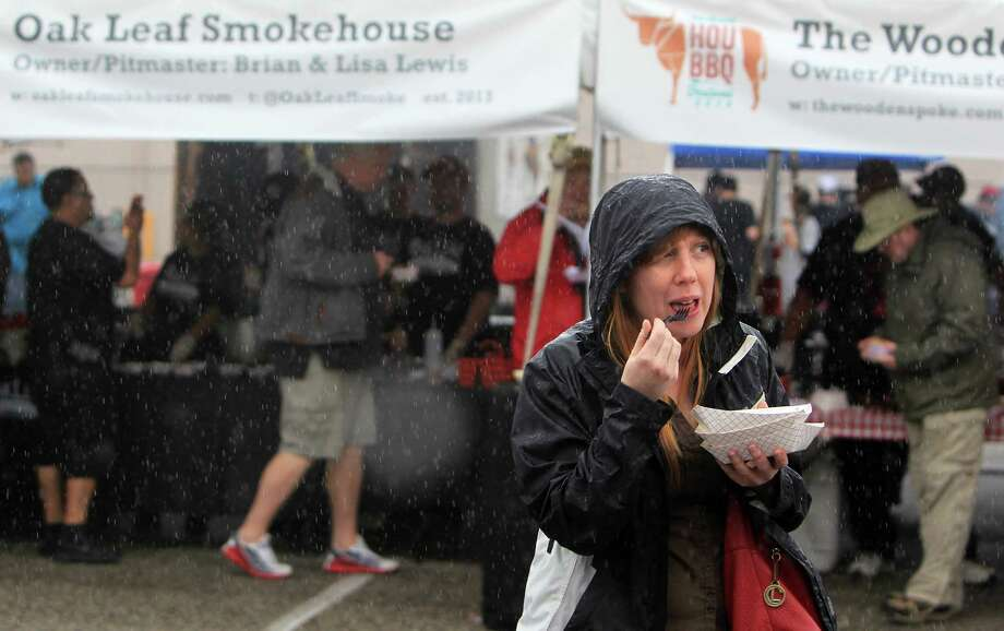 Anne Marie Schwartz looks for shelter from the rain during The 2nd Annual BBQ Cook Off on April 6,  2014, in Houston, Tx. The Houston Barbecue Festival is to celebrate and recognize owners and pit masters that make Houston barbecue unique. Photo: Mayra Beltran, Houston Chronicle / © 2014 Houston Chronicle