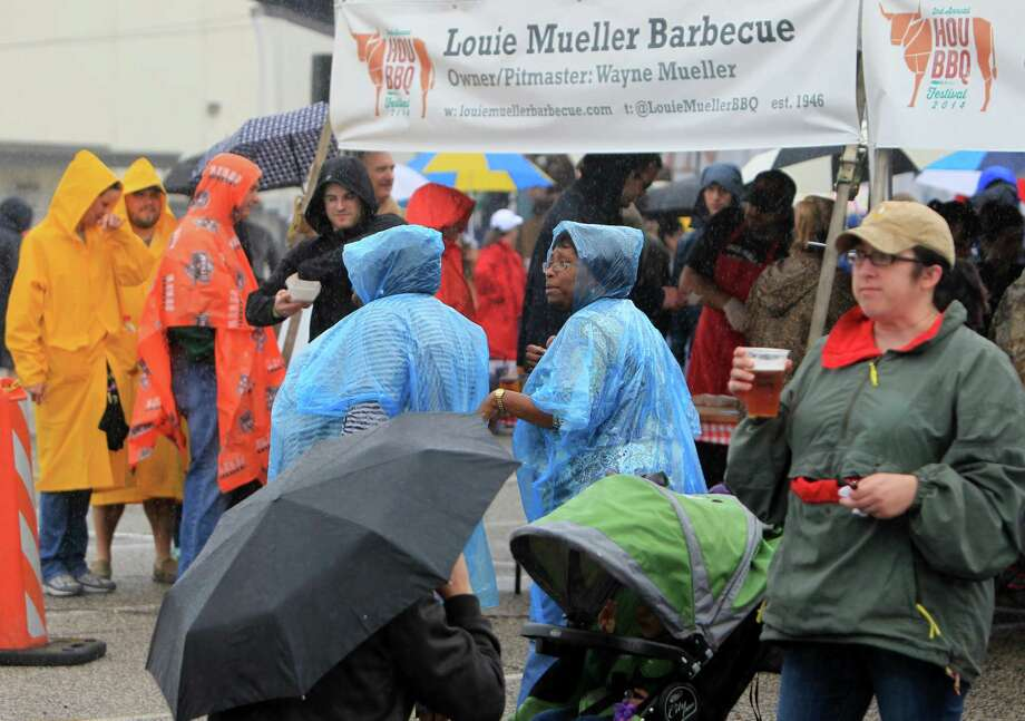 A sea of umbrellas, ponchos, and rain coats can be seen throughout The 2nd Annual BBQ Cook Off while attendants wait in line for their food sample at Reliant on April 6,  2014, in Houston, Tx. The Houston Barbecue Festival is to celebrate and recognize owners and pit masters that make Houston barbecue unique. Photo: Mayra Beltran, Houston Chronicle / © 2014 Houston Chronicle
