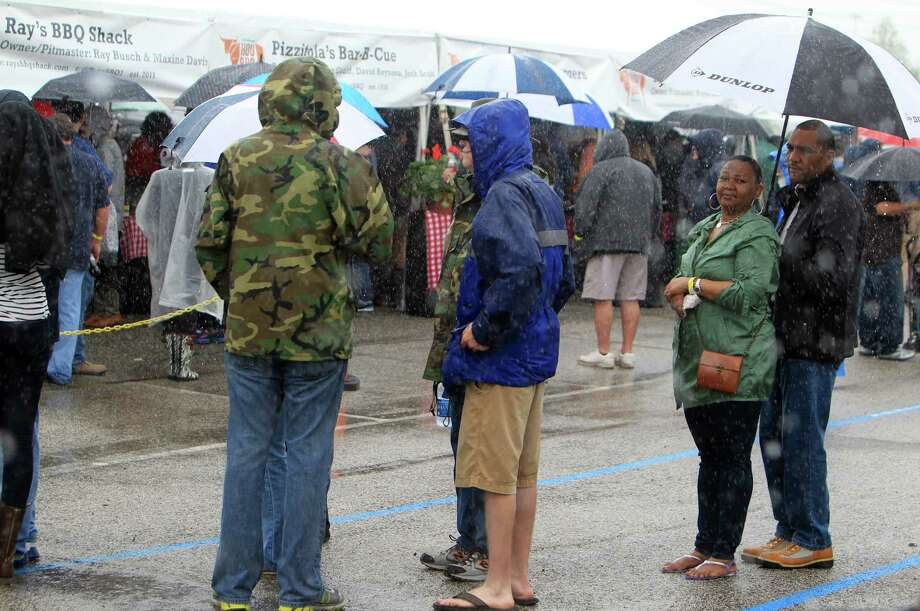 BBQ enthusiast do not shy away from rain while standing in line for their sample during The 2nd Annual BBQ Cook Off on April 6,  2014, in Houston, Tx. The Houston Barbecue Festival is to celebrate and recognize owners and pit masters that make Houston barbecue unique. Photo: Mayra Beltran, Houston Chronicle / © 2014 Houston Chronicle