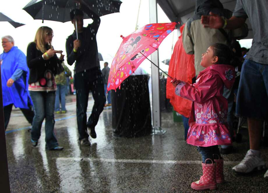 Amaris Martinez, 4, and her father shelter from the rain under a tent during The 2nd Annual BBQ Cook Off at Reliant on April 6,  2014, in Houston, Tx. The Houston Barbecue Festival is to celebrate and recognize owners and pit masters that make Houston barbecue unique. Photo: Mayra Beltran, Houston Chronicle / © 2014 Houston Chronicle