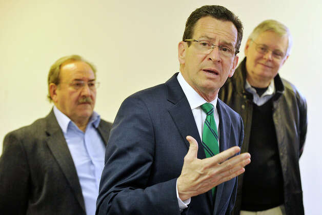 Gov. Dannel P. Malloy addresses a crowd of supporters as Democratic City Committee Chairman John Mallozzi, left, and Mayor David Martin look on during the governor's campaign kickoff party at the Democratic City Committee headquarters in Stamford, Conn., on Sunday, April 6, 2014. Photo: Jason Rearick / Stamford Advocate