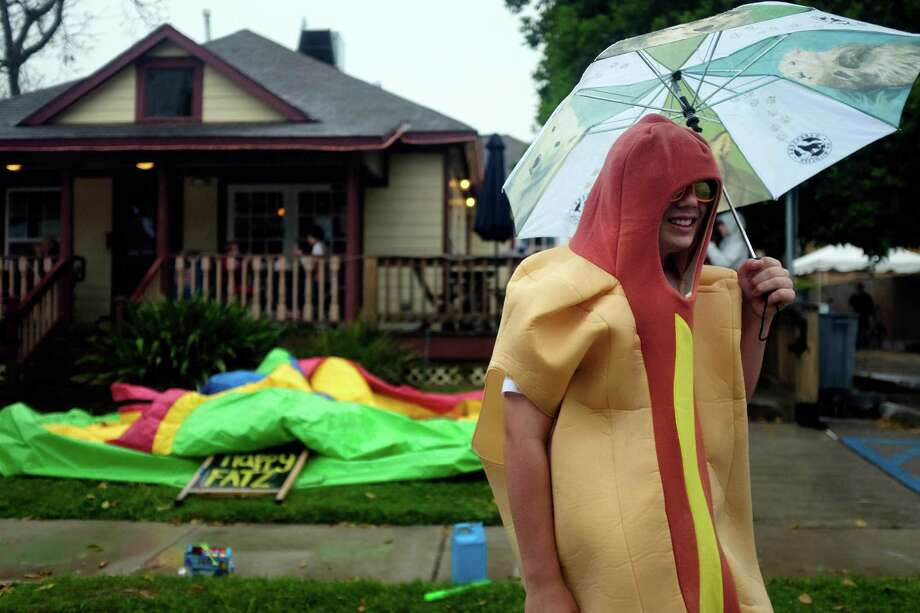 "Dressed in a hot dog suit and dawning an umbrella to keep him dry, Dylan Bowen, urges passersby to try Happy Fatz, a gourmet hotdog restaurant on White Oak Blvd, during one of the first Sunday Streets HTX events, Sunday, April 6, 2014 in The Heights neighborhood of Houston, Texas. Sunday Streets HTX is an opportunity for families and neighbors to be outside and celebrate the streets of Houston,"" said Mayor Annise Parker. ""This pilot initiative meets many of the goals of my Go Healthy Houston program, encouraging more recreation and physical activity in Houston, in a family friendly environment. The program will open streets to bicyclists and pedestrians for recreation and physical activity.   TODD SPOTH Photo: TODD SPOTH, Photographer / © TODD SPOTH"
