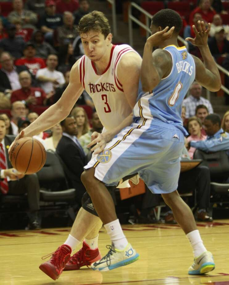 Omer Asik moves around Aaron Brooks. Photo: Melissa Phillip, Houston Chronicle