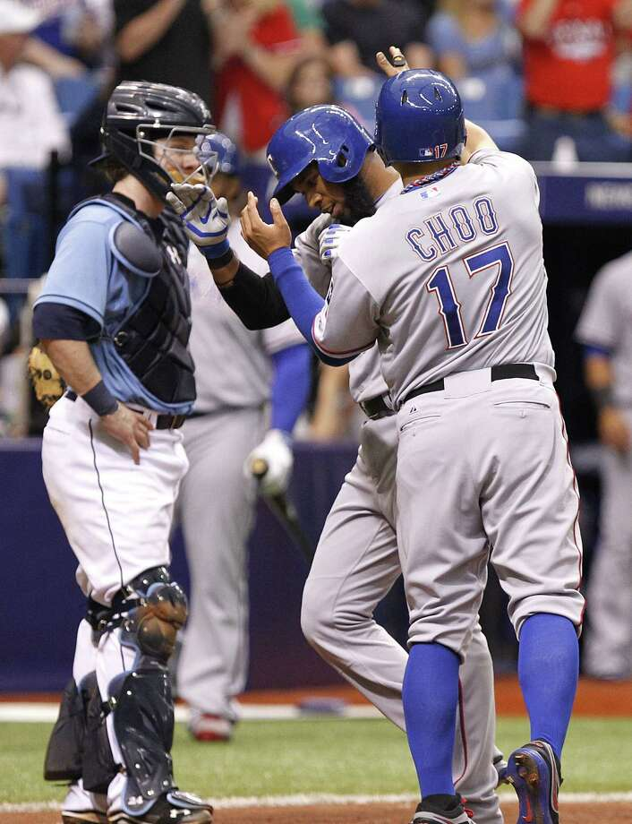 The Rangers' Elvis Andrus (center) is congratulated by Shin-Soo Choo after his two-run homer in the eighth as Rays catcher Ryan Hanigan watches. Photo: Brian Blanco / Getty Images / 2014 Getty Images