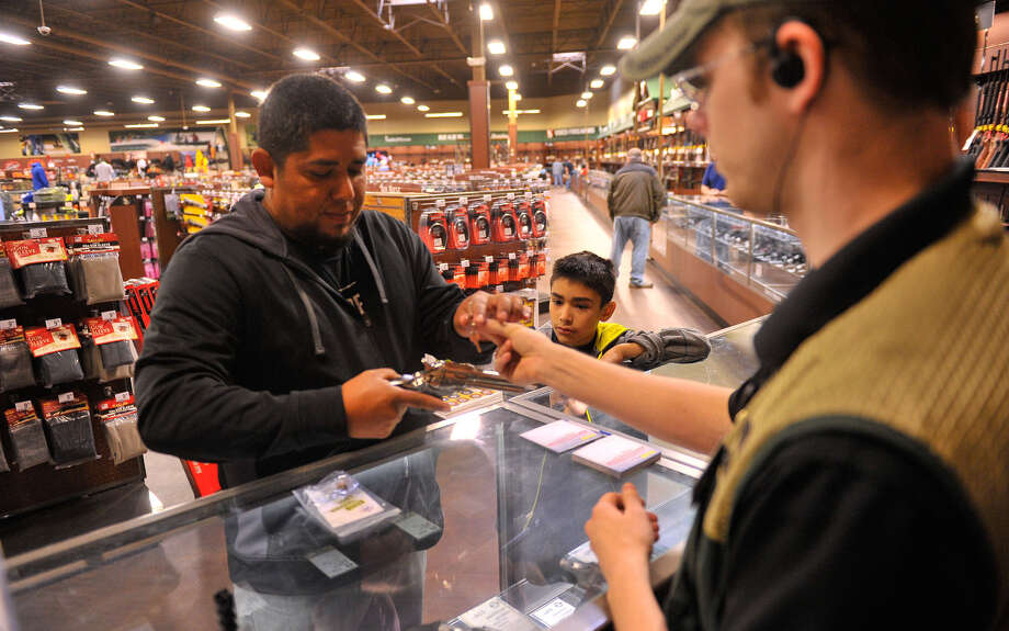 Fernando Quintanilla and his son Ferny check out their free trigger lock from Gander Mountain's Drew Berg at the San Antonio store at 8203 Highway 151 Sunday. Photo: Robin Jerstad / For The San Antonio Express-News