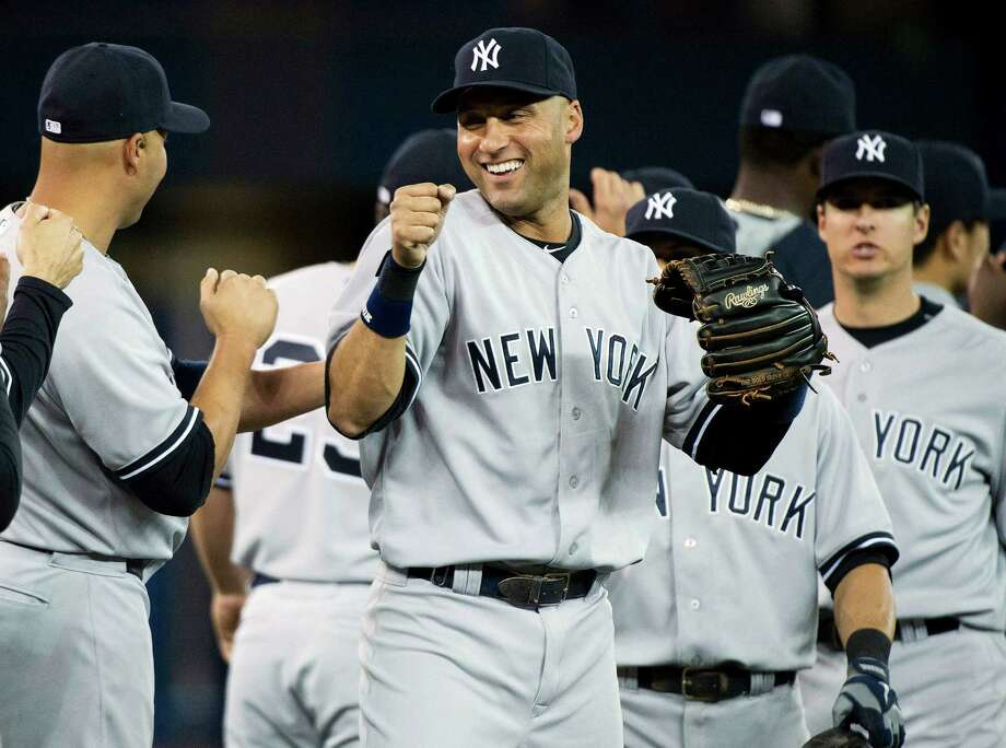 New York Yankees shortstop Derek Jeter, center, celebrates with his teammates after defeating the Toronto Blue Jays during the ninth inning of a baseball game in Toronto on Sunday, April 6, 2014.  (AP Photo/The Canadian Press, Nathan Denette) ORG XMIT: NSD117 Photo: Nathan Denette / The Canadian Press