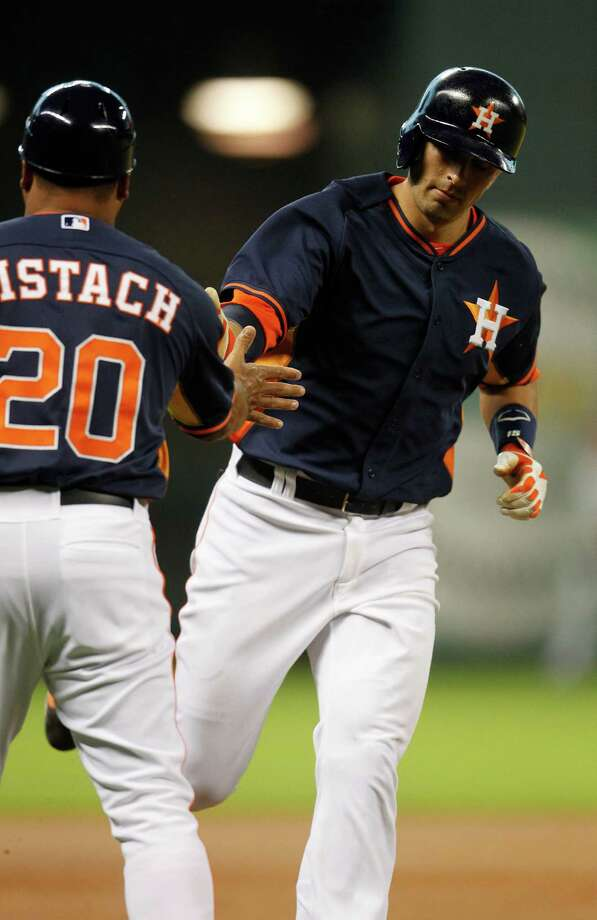 Drawing kudos from third-base coach Pat Listach (20), Jason Castro heads home in the first inning after hitting the first of the Astros' five homers in Sunday's win at Minute Maid Park. Photo: Karen Warren, Staff / © 2014 Houston Chronicle
