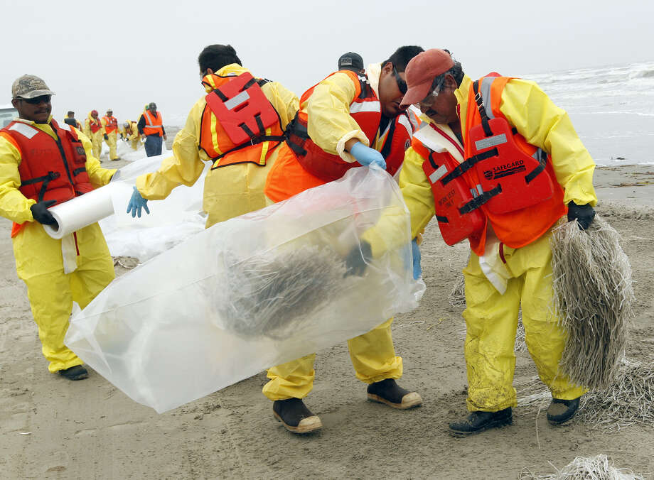 Oil spill response crews remove absorbent material on the beach in Galveston. About 170,000 gallons of oil spilled into Galveston Bay on March 22. Photo: Jennifer Reynolds / Galveston County Daily News / The Galveston County Daily News