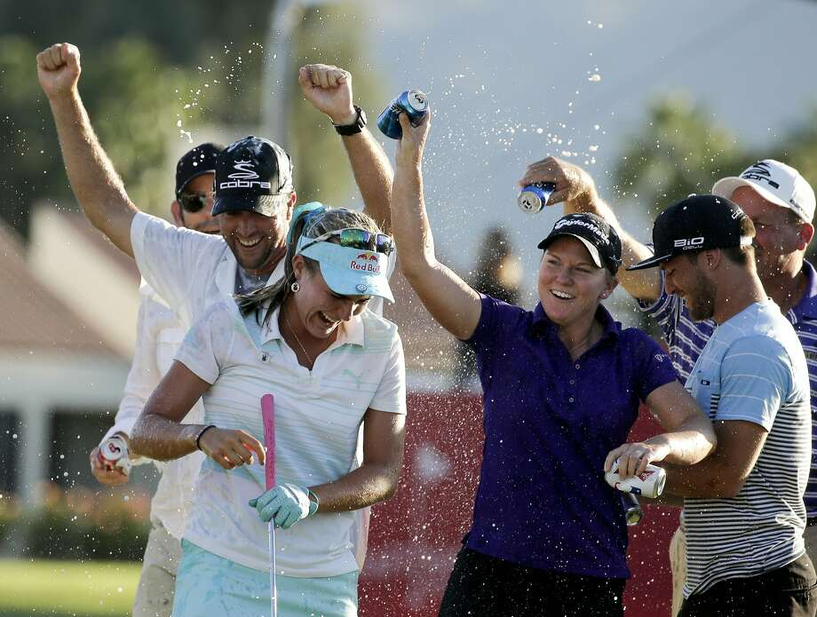 Lexi Thompson, left, is showered after winning the Kraft Nabisco. Soon after, she jumped in the pond. Photo: Chris Carlson, Associated Press