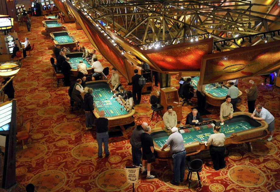 FILE - In this Sept. 18, 2013 file photo, patrons play craps at tables at Mohegan Sun in Uncasville, Conn. A gaming slump is eating into the profits of Mohegan Sun in 2014, but the 2,000 tribal members who draw benefits from the massive casino are not feeling the pinch. The tribe's gaming company has begun running casinos in Pennsylvania and Atlantic City, and it is pursuing more projects in states including Washington, New York, and Massachusetts. (AP Photo/Jessica Hill, File) ORG XMIT: BX302 Photo: Jessica Hill / FR125654 AP