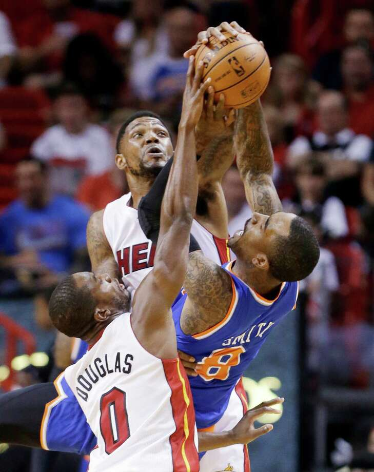 Miami Heat forward Udonis Haslem, rear, and guard Toney Douglas (0) prevent a pass by New York Knicks guard J.R. Smith (8) during the first half of an NBA basketball game, Sunday, April 6, 2014, in Miami. (AP Photo/Wilfredo Lee) ORG XMIT: AAA104 Photo: Wilfredo Lee / AP
