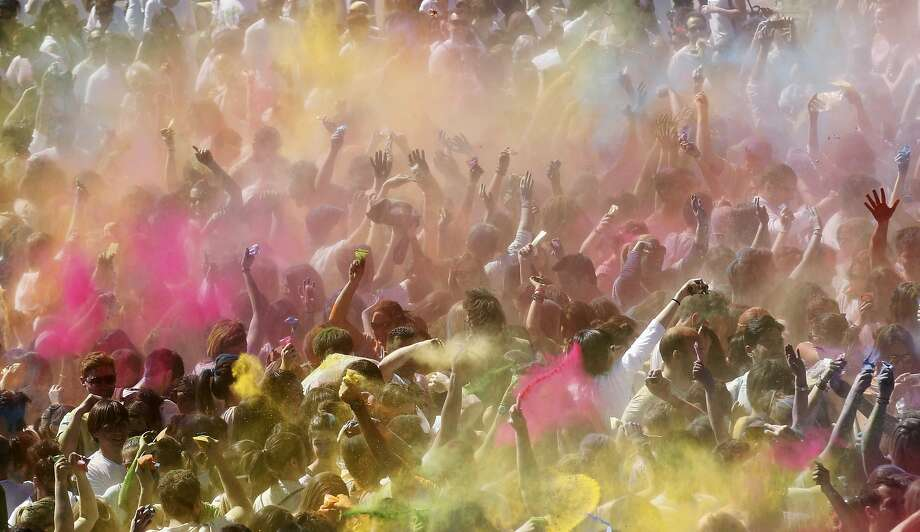 People throw coloured powder during the Holi festival in Barcelona April 6, 2014. REUTERS/Albert Gea (SPAIN - Tags: SOCIETY) Photo: Albert Gea, Reuters