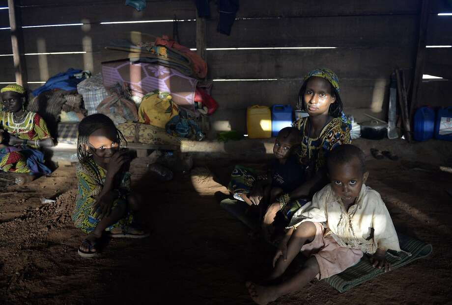 Women and children of the Pulaar ethnic group sit in a house in the village of Boda on April 6, 2014. Members of the Pulaar ethnic group and the Muslim community are trapped in the village of Boda, surrounded by the Christian anti-Balaka militias and protected by the French troops of Operation Sangaris and African-led International Support Mission to the Central African Republic (MISCA) forces.  AFP PHOTO / MIGUEL MEDINAMIGUEL MEDINA/AFP/Getty Images Photo: Miguel Medina, AFP/Getty Images
