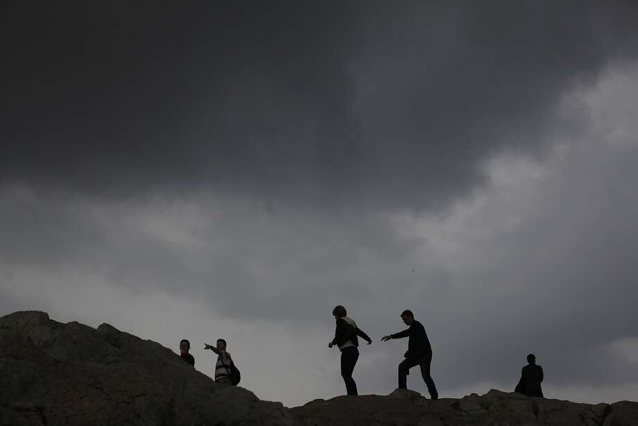 People walk at the foot of the Acropolis hill as dark clouds cover the sky in Athens on Sunday, April 6, 2014. Rainstorms afflicted most of Greece Sunday after clear skies during the previous weeks. (AP Photo/Kostas Tsironis) Photo: Kostas Tsironis, Associated Press