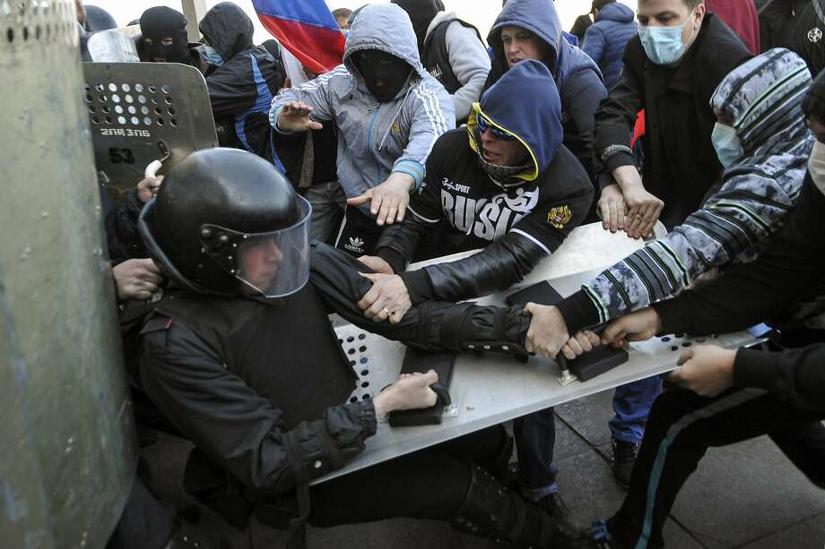 Pro-Russian protesters scuffle with a policeman near the regional government building in Donetsk April 6, 2014. Around 100 pro-Russian protesters stormed the regional government building in the eastern Ukrainian city of Donetsk on Sunday and hung up a Russian flag in defiance of Kiev's pro-European government.  REUTERS/Mikhail Maslovsky (UKRAINE - Tags: POLITICS CIVIL UNREST) Photo: Stringer, Reuters