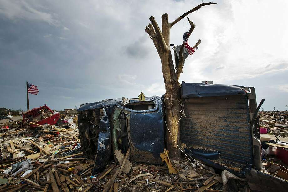 "The body of a pickup truck is wrapped around a tree trunk after being thrown there by by a tornado in Moore, Oklahoma in this file photo from May 25, 2013. In 2014, Moore, in the heart of the so-called ""Tornado Alley"" where twisters frequently hit, will be operating under a new set of building codes seen as some of the most stringent in the nation to protect people and structures from deadly winds.  REUTERS/Lucas Jackson/Files (UNITED STATES - Tags: DISASTER ENVIRONMENT) Photo: Lucas Jackson, Reuters"