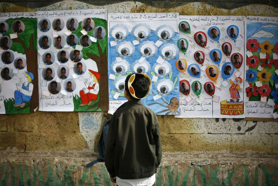 A Yemeni student looks at pictures of his colleagues hanging on a wall as he attends his daily classes at a school in Sanaa, Yemen, Sunday, April 6, 2014.  (AP Photo/Hani Mohammed) Photo: Hani Mohammed, Associated Press