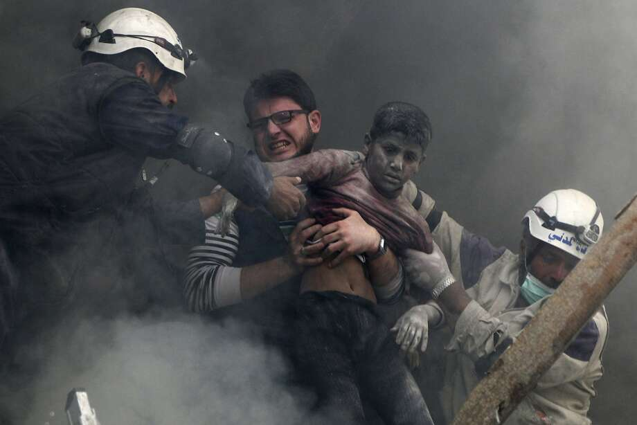 ATTENTION EDITORS - VISUAL COVERAGE OF SCENES OF INJURY OR DEATH  Men rescue a boy from under the rubble after what activists said was explosive barrels dropped by forces loyal to Syria's President Bashar Al-Assad in Al-Shaar neighbourhood of Aleppo April 6, 2014. REUTERS/Hosam Katan (SYRIA - Tags: POLITICS CIVIL UNREST CONFLICT TPX IMAGES OF THE DAY) Photo: Hosam Katan, Reuters