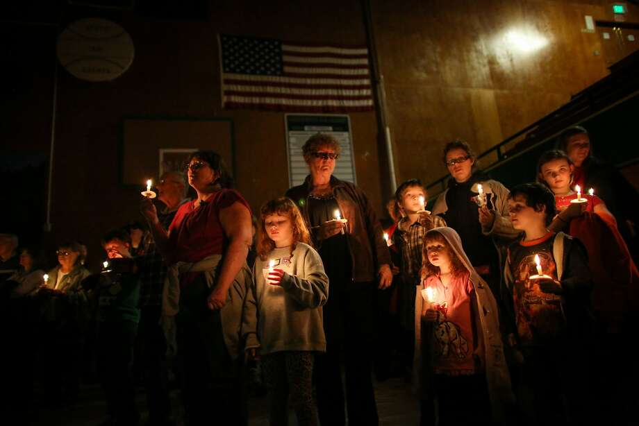 People hold candles during a vigil at the Darrington Community Center on Saturday, April 5, 2014. The vigil was held on the two week anniversary of the Oso mudslide and brought together hundreds of local residents affected by the disaster. (AP Photo/seattlepi.com, Joshua Trujillo) Photo: Joshua Trujillo, Associated Press