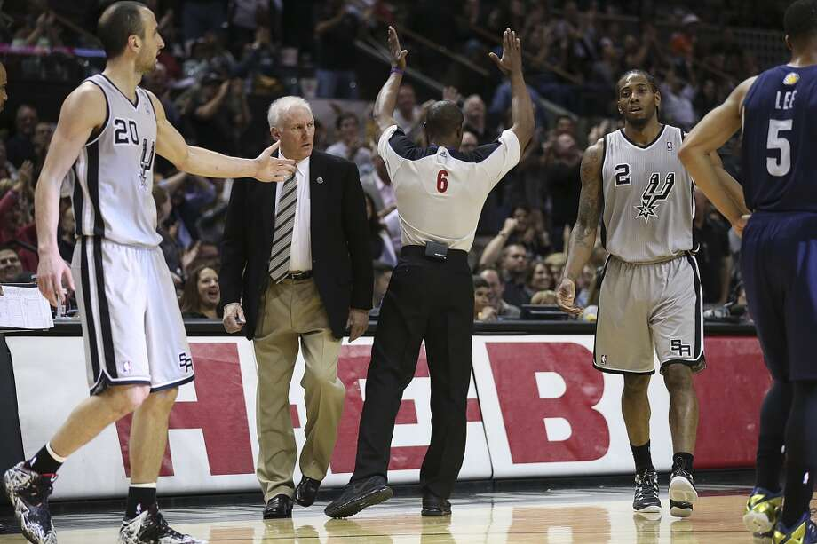 San Antonio Spurs head coach Gregg Popovich looks over at Kawhi Leonard after he sank a three-pointer to end the first half against the Memphis Grizzlies at the AT&T Center, Sunday, April 6, 2014. Photo: San Antonio Express-News