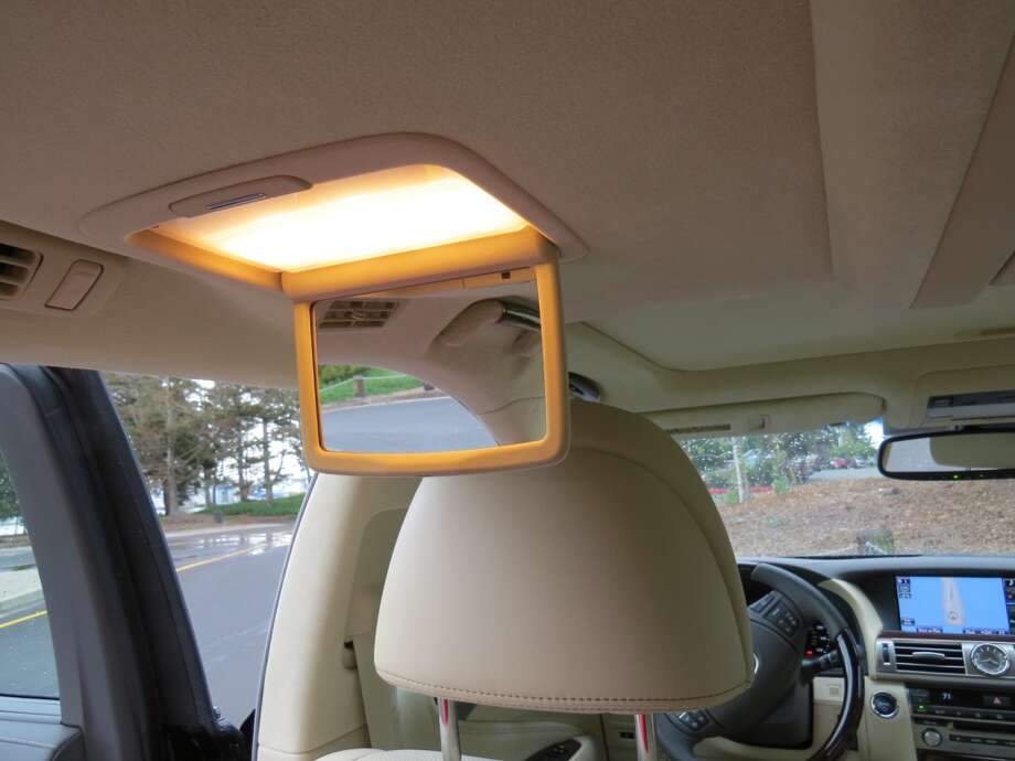 A drop-down vanity mirror for a back seat passenger.