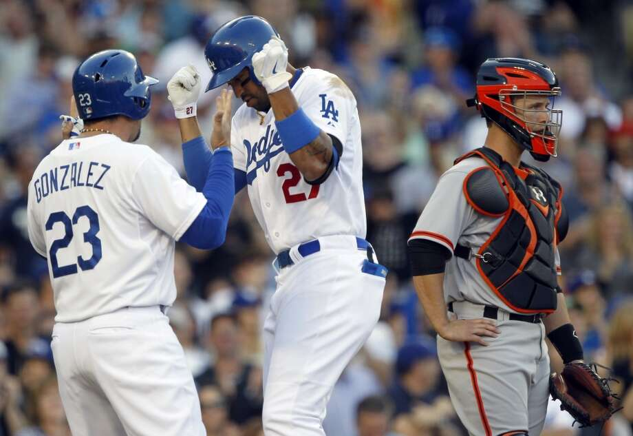 Los Angeles Dodgers' Adrian Gonzalez, left, congratulates Matt Kemp, center, for hitting a two-run home run, as San Francisco Giants catcher Buster Posey (28) looks away, in the fourth inning of a baseball game on Sunday, April 6, 2014, in Los Angeles. It was Kemp's second home run of the game. Photo: Alex Gallardo, Associated Press