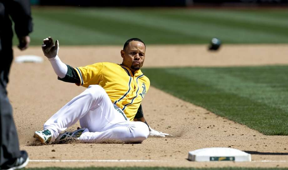 A's Coco Crisp, (4) slides safely into third base after hjis triple to right in the 6th innig, as the Oakland Athletics went on to lose to the Seattle Mariners 3-1 at the O.co Coliseum on Saturday April 5, 2014, in Oakland, Calif. Photo: The Chronicle