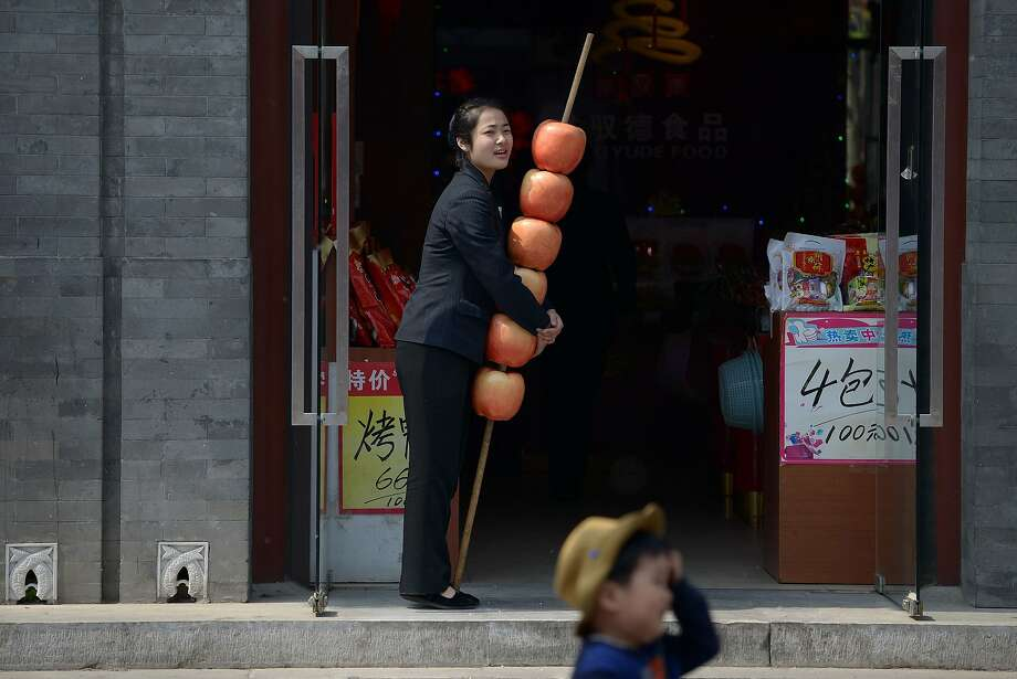 Shop prop: A saleswoman hugs a shish kebab of oversized apples as she waits for customers at her store in Beijing. Photo: Wang Zhao, AFP/Getty Images