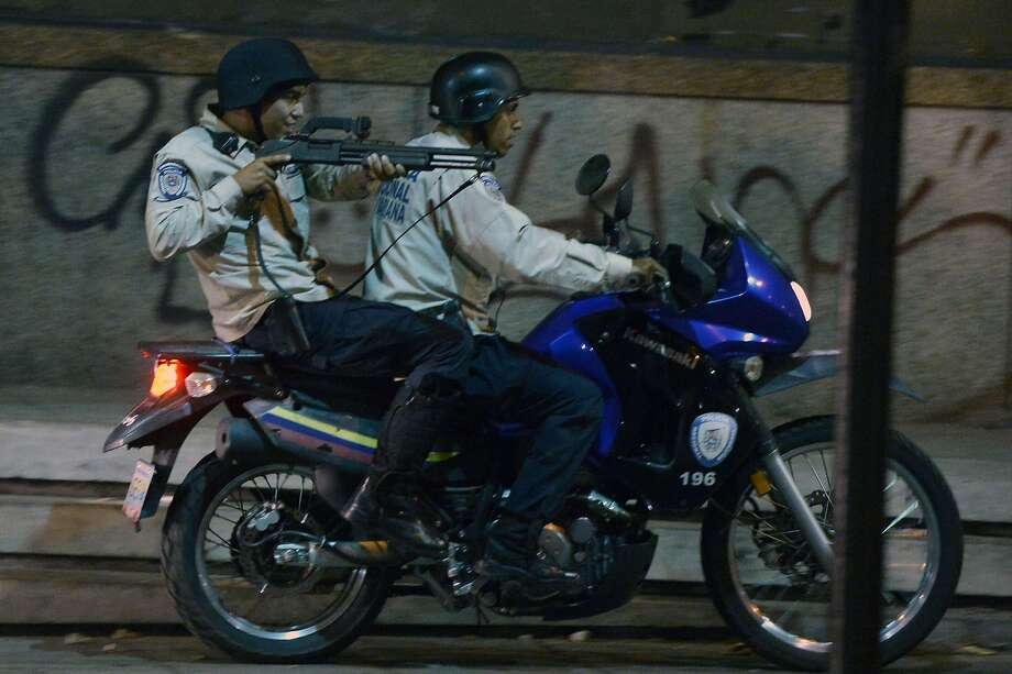 Riding shotgun:A motorcycle cop man aims a shotgun while his partner steers the bike during clashes with opposition activists in Caracas. Venezuela's attorney general formally   charged jailed opposition leader Leopoldo Lopez with criminal incitement in the anti-government protests that have roiled the country for two months. He faces up to 14 years in prison. Photo: Juan Barreto, AFP/Getty Images