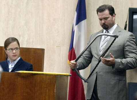 Defense attorney Chip Lewis, right, shows state DNA analyst April Orbison-Broesche a bow-saw entered into evidence in the murder trial of millionaire Robert Durst on Oct. 1, 2003, in Galveston. Testimony showed Durst used it to cut up and dispose of his neighbor's body. Photo: PAT SULLIVAN, Houston Chronicle / AP