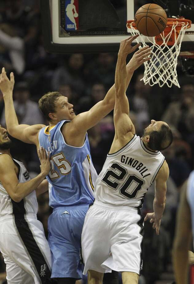 San Antonio Spurs' Manu Ginobili goes for a rebound against Denver Nuggets' Timofey Mozgov during the first half at the AT&T Center, Wednesday, March 26, 2014. Photo: Jerry Lara, San Antonio Express-News