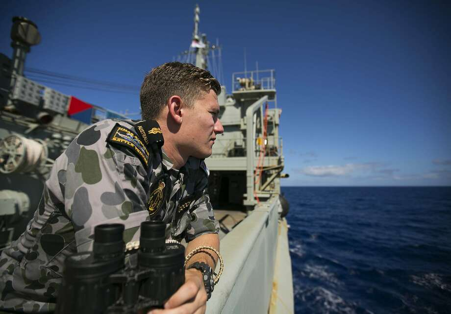 Marine Technician Trent Goodman keeps watch aboard an Australian vessel. Photo: Abis Julianne Cropley, AFP/Getty Images