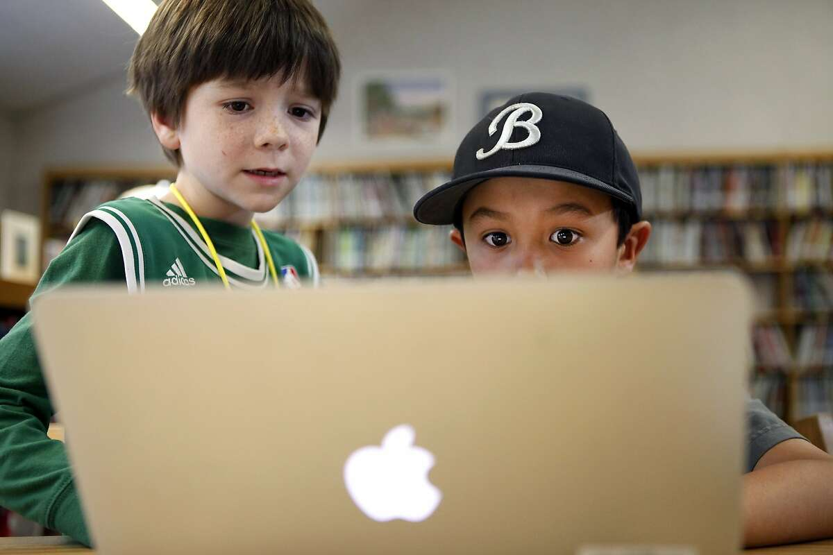 Second-graders Cole Donnelly (far left) and James Bonneau, and first-grader Caitlin Chin, above, work on a coding lesson in the after-school computer class at Old Mill School in Mill Valley.