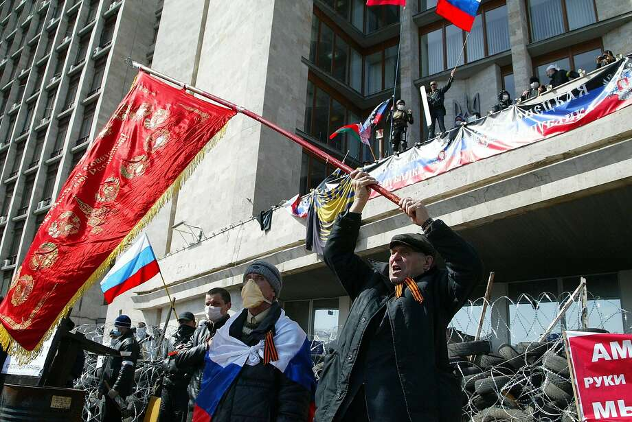 Activists calling for secession wave an old Soviet flag and Russian national flags in front of a barricade at the regional administration building in Donetsk. Photo: Alexander Ermochenko, Associated Press