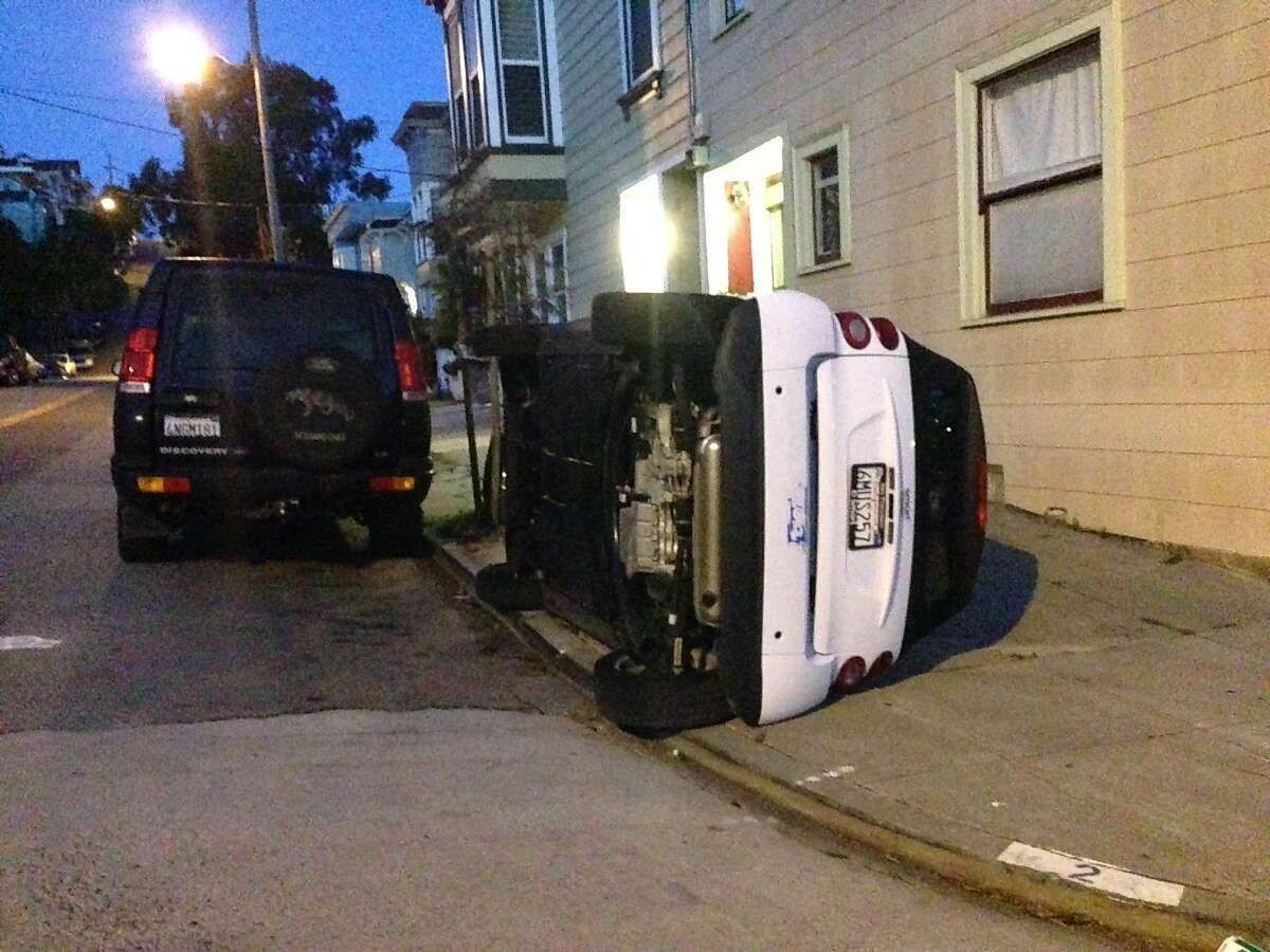 A vandalized Smart Car is seen tipped over on the corner of Prospect and Coso Avenues early Monday morning in Bernal Heights, San Francisco, Calif.