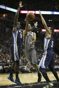 San Antonio Spurs' Tony Parker shoots between Memphis Grizzlies' Zach Randolph, left, and Courtney Lee during the first half at the AT&T Center, Sunday, April 6, 2014. Photo: Jerry Lara, San Antonio Express-News