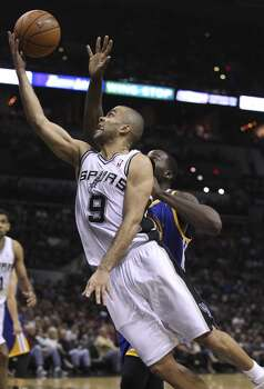 Spurs' Tony Parker (09) leans in for a layup against Golden State Warriors' Draymond Green (23) in the second half at the AT&T Center on Wednesday, Apr. 2, 2014. Spurs defeated the Warriors, 111-90. Photo: Kin Man Hui, San Antonio Express-News