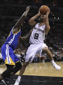 Spurs' Tony Parker (09) steps back for a shot against Golden State Warriors' Draymond Green (23) in the second half at the AT&T Center on Wednesday, Apr. 2, 2014. Spurs defeated the Warriors, 111-90. Photo: Kin Man Hui, San Antonio Express-News