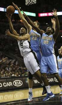 San Antonio Spurs' Tony Parker shoots under pressure from Denver Nuggets' Timofey Mozgov, (25), and Kenneth Faried during the first half at the AT&T Center, Wednesday, March 26, 2014. Photo: Jerry Lara, San Antonio Express-News