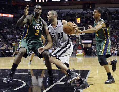 San Antonio Spurs' Tony Parker looks for room between Utah Jazz's Marvin Williams (left) and Trey Burke during second half action Sunday March 16, 2014 at the AT&T Center. The Spurs won 122-104. Photo: Edward A. Ornelas, San Antonio Express-News